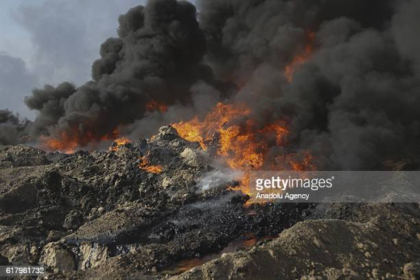 Black smoke rises after an oil well set on fire in the center of al-Kayyara town to the south of Daesh terror organization-held Mosul in Iraq on...