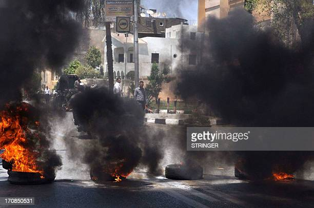 Black smoke rises from tires set on fire by demonstrators outside the Luxor town house protesting against the appointment of Adel alKhayat a member...