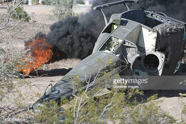 Black smoke rises to the air from a simulated wreckage of a downed UH-1N Huey.