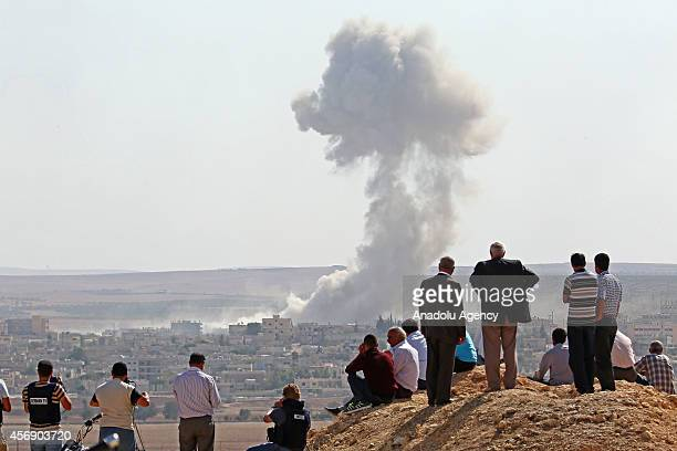 Black smoke, rising in Ayn al-Arab after airstrikes staged by US-led coalition air forces, is seen from Suruc district of Turkey's Sanliurfa on...