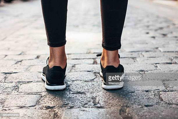 Black sneakers of sportive young woman, close-up