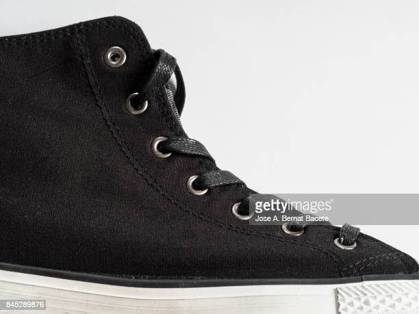 black sneakers  on a white background, with form of boot - basketball shoe stock photos and pictures
