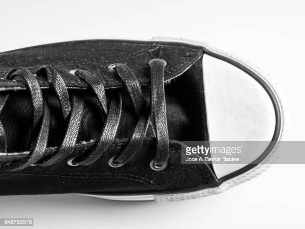 black sneakers  on a white background, with form of boot - sapato preto - fotografias e filmes do acervo