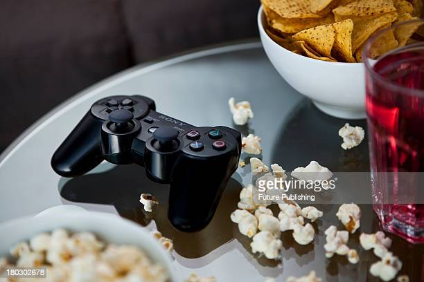 A black Sony PlayStation 3 wireless controller photographed on a glass table surrounded by bowls of snacks taken on July 9 2013