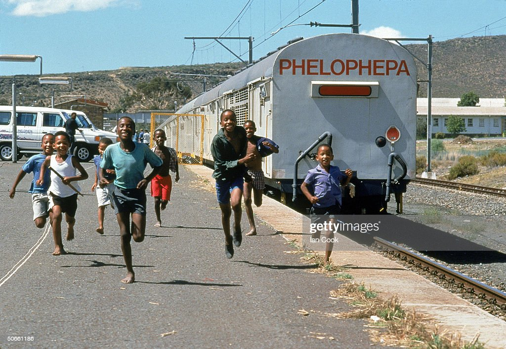 Black South African children running alongside tracks where medical train Phelophepa, founded by white South African Lynette Coetzee to bring medicine & health education to all S. Africans regardless of race.