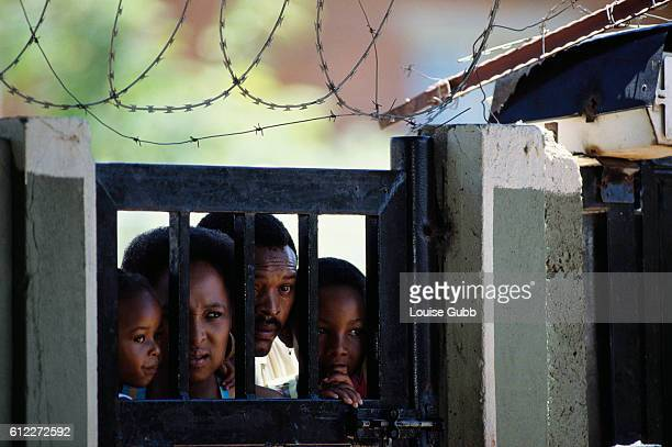 A Black South African family peers through Nelson Mandela's gate for a glimpse of the former African National Congress President after he was...