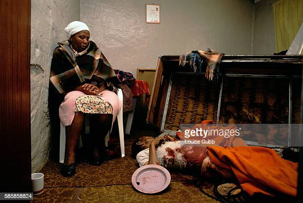 A Black South African woman grieves death of her brother who lies dead on the floor near her after night of apartheid killings by Zulu hostel...