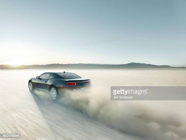 black sports car driving on dry lake bed - faire la course photos et images de collection
