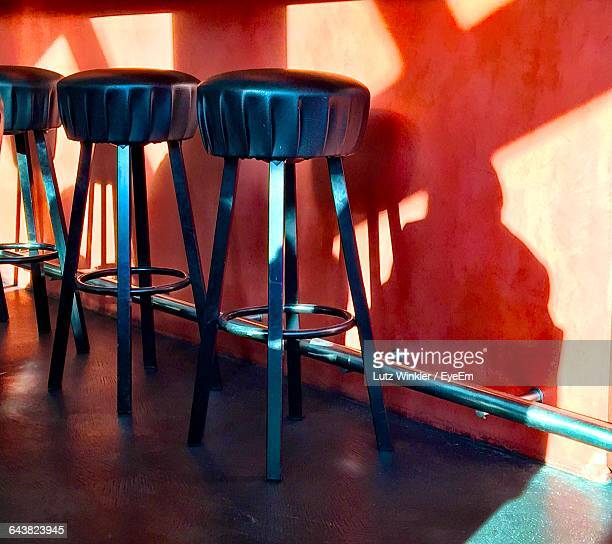 Black Stools By Bar Counter With Sunlight