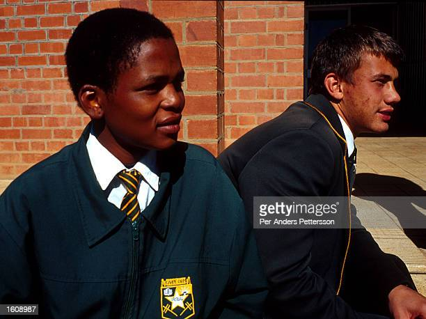 A black student and a white student sit on the campus June 21 2001 of Vryburg High School in Vryburg South Africa Vryburg a small and very...