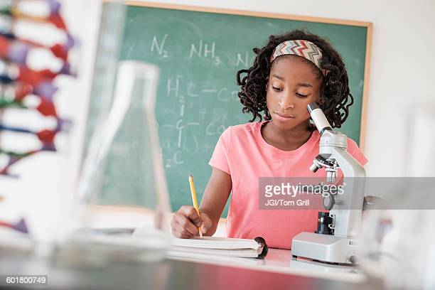 Black student performing experiment in science class