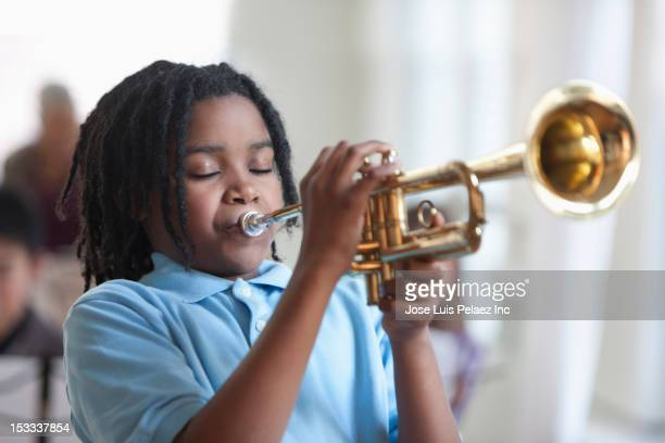 black student playing trumpet in music class - trumpet stock pictures, royalty-free photos & images