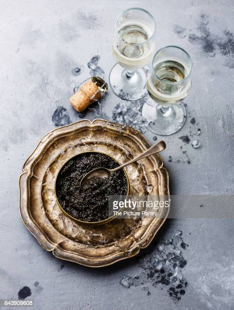 Black Sturgeon caviar in can on ice and champagne on concrete background