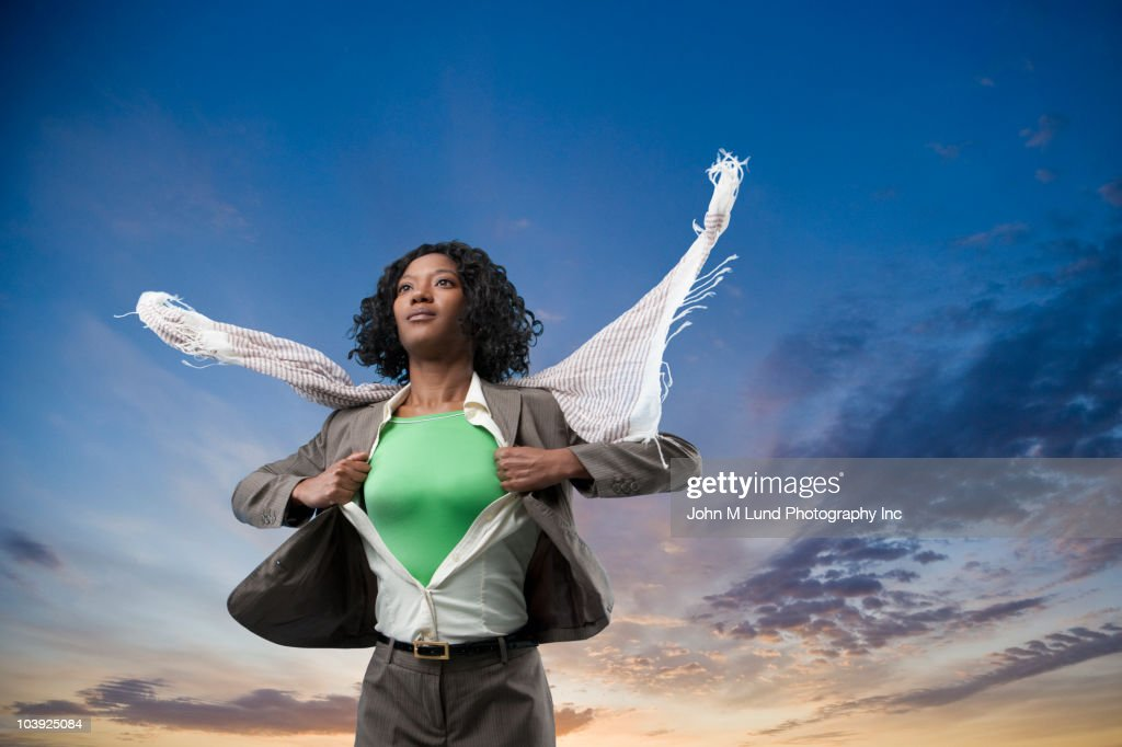 Black superhero changing clothes outdoors : Stock Photo