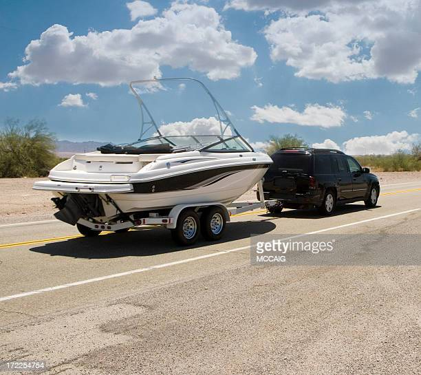 A black SUV is hauling a white motor boat for boating trip
