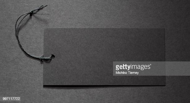 black tag on black paper - whistle blackboard stock pictures, royalty-free photos & images