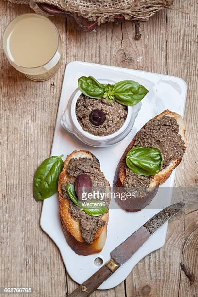 Black tapenade in bowl, crostinis with olive paste