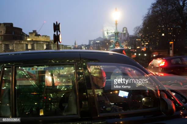 Black taxi driver sitting in his cab waiting in traffic in the rain at Tower Hill in London England United Kingdom