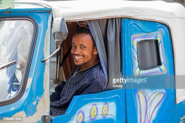 Black taxi driver smiling in tuk-tuk / auto rickshaw in the city Awasa / Awassa / Hawassa, Great Rift Valley, Southern Ethiopia, Africa.