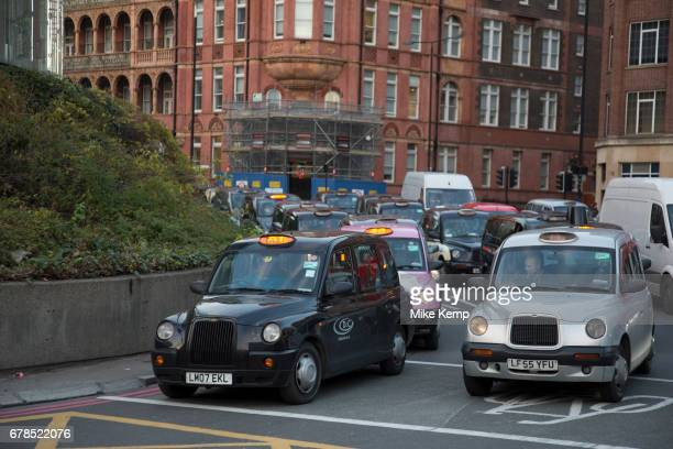Black taxi drivers protest against taxi service app Uber blocking Waterloo Joined in many numbers by future black cab drivers on mopeds currently...