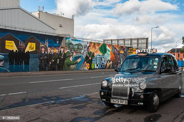 black taxis provide visitors with tailored tours of the belfast murals - belfast murals photos et images de collection