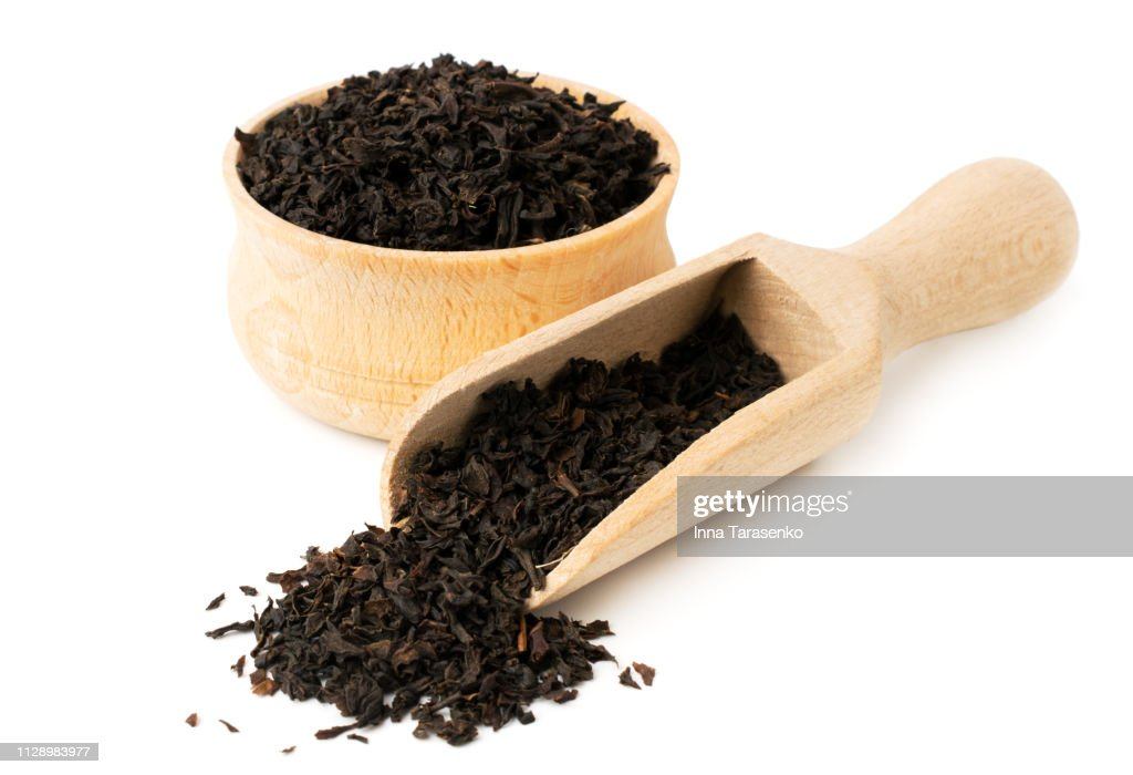 Black tea leaves in wooden plate and spoon on a white : Stock Photo
