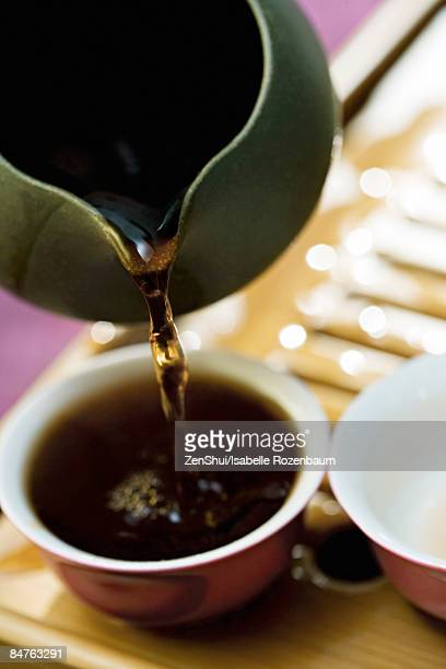black tea poured from teapot into cup on bamboo tea tray - black bamboo stock pictures, royalty-free photos & images