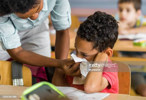 black teacher assisting schoolboy in nose blowing at elementary school. - influenza virus foto e immagini stock