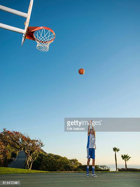 Black teenage boy shooting basketball on court