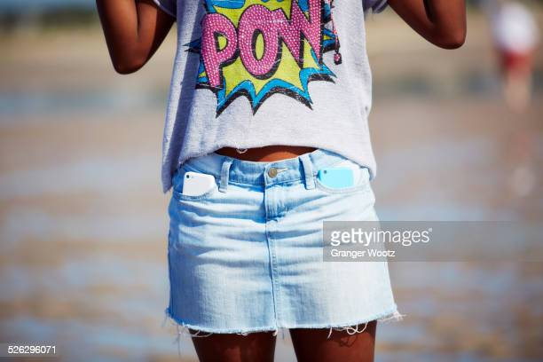 Black teenage girl carrying two cell phones in skirt pockets on beach