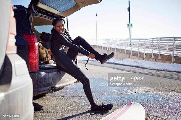 Black teenage girl putting on wetsuit