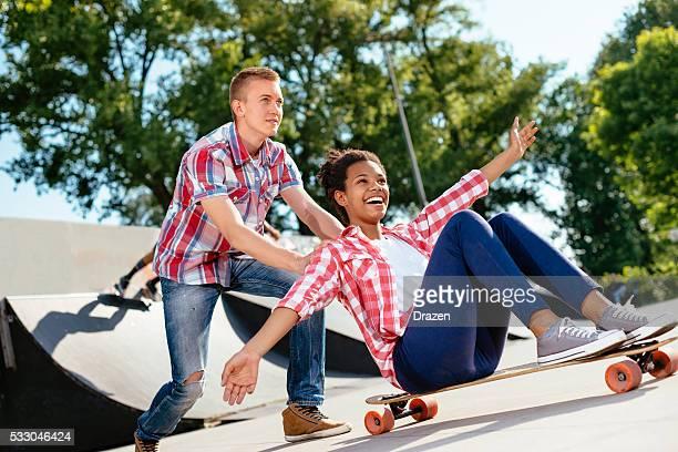 Adolescente noire et Caucasien garçon passer du temps dans Parc de skate