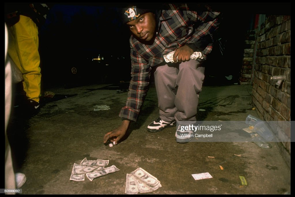 black teenager cash in hand picking up dice while gambling on