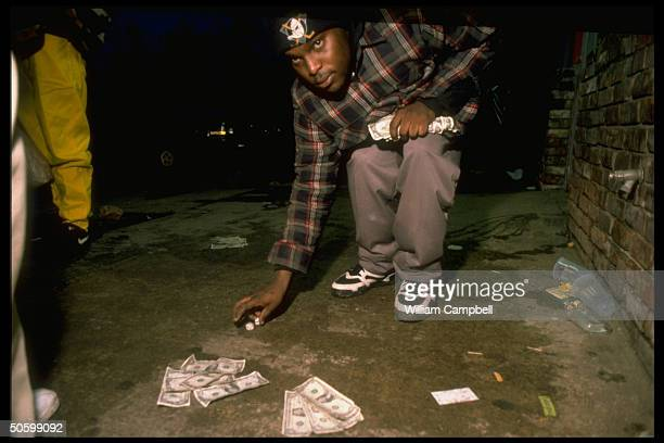Black teenager cashinhand picking up dice while gambling on nightdim street re hard times for town named in Census figures as poorest in US