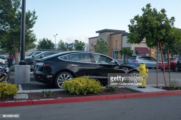 Black Tesla Model 3 electric car from Tesla Motors parked in a parking lot at a shopping mall in Dublin California May 21 2018