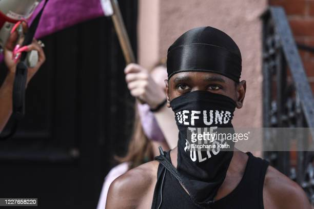 """Black trans liberation activist wears a bandana that reads """"Defund the Police"""" in front of the Stonewall Inn on July 16, 2020 in New York City...."""