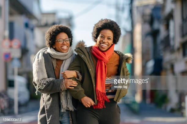 black twin sisters walking in street arm in arm happily - sister stock pictures, royalty-free photos & images