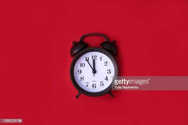 black vintage alarm clock on red background. time concept. copy space. - 真夜中 ストックフォトと画像