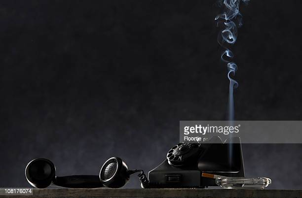 black: vintage telephone and cigarette in ashtray on table - film noir style stock pictures, royalty-free photos & images
