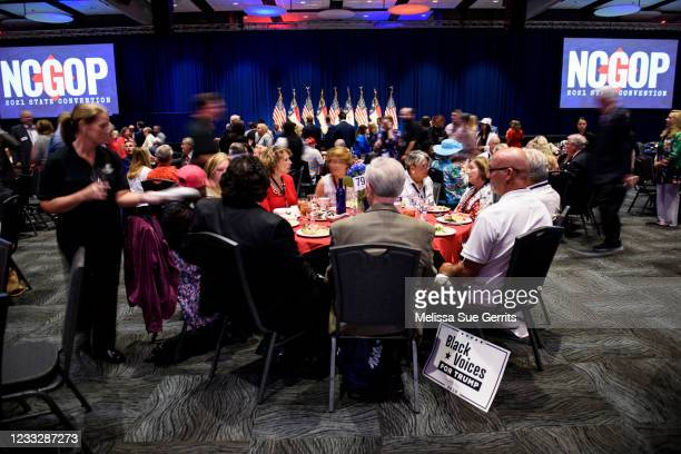 """Black Voices for Trump"""" sign is seen next to attendees of the North Carolina GOP convention on June 5, 2021 in Greenville, North Carolina. Former..."""