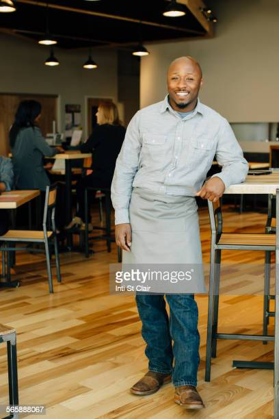Black waiter smiling in in cafe