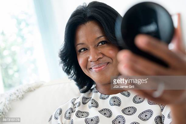 Black woman admiring herself in compact mirror