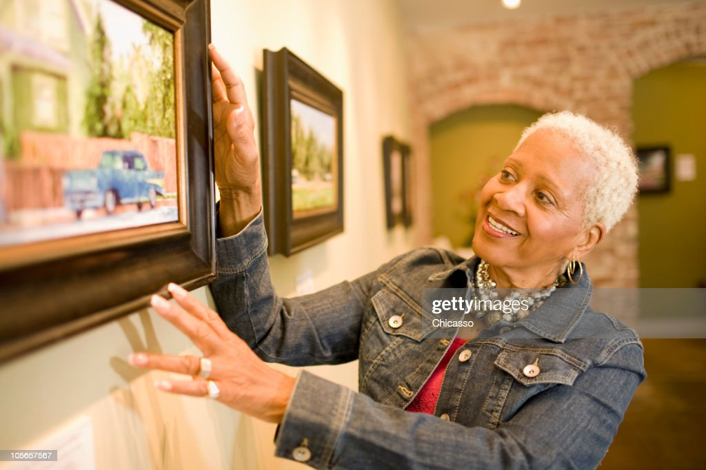 Black woman admiring painting in gallery : Stock Photo