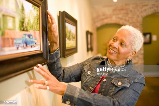 Black woman admiring painting in gallery