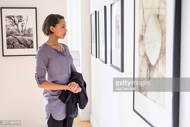 Black woman admiring paintings in art gallery