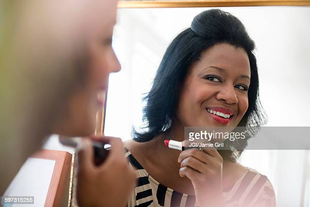 black woman applying lipstick in mirror - admiration stock pictures, royalty-free photos & images