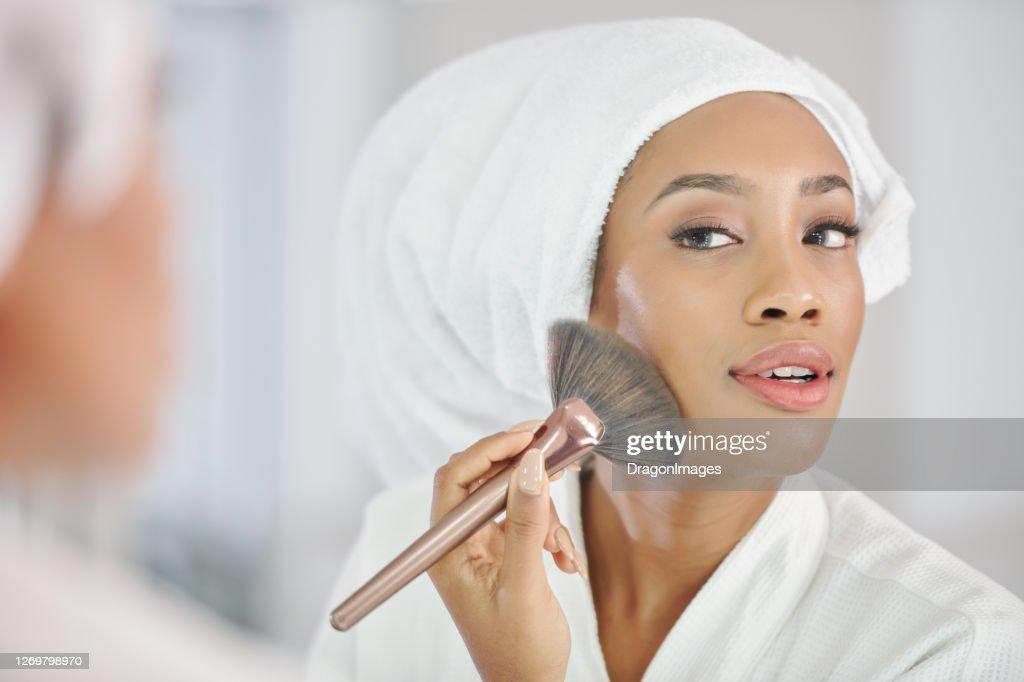 Black woman applying make-up : Stock Photo