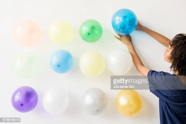 black woman attaching balloons to wall - party decoration stock pictures, royalty-free photos & images