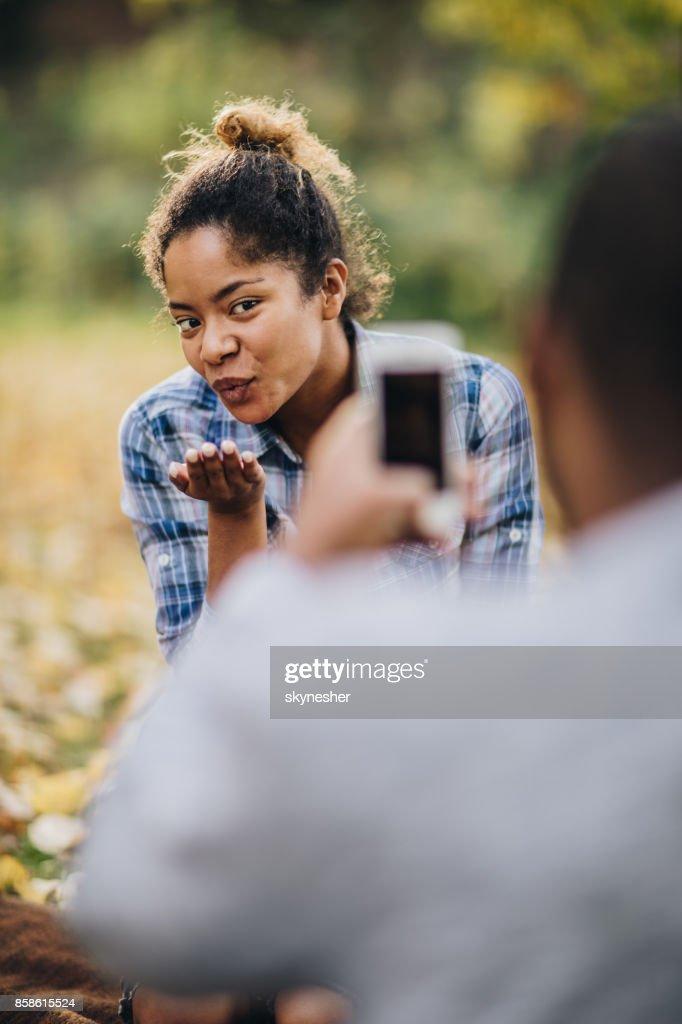 Schwarze Frau bläst einen Kuss während fotografiert in der Natur. : Stock-Foto