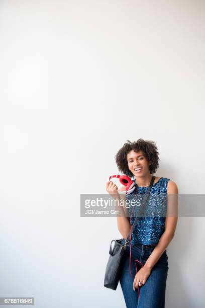 Black woman carrying purse holding headphones